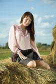Pretty girl on straw bale — Stock Photo