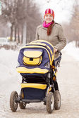 Woman with pram in winte — Stock Photo