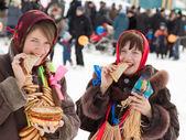 Happy girls eating pancake during Shrovetide — Stock Photo
