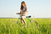 Girl riding bicycle in field — Стоковое фото