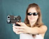 Girl aiming a black gun — Stock Photo