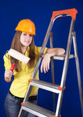 Girl in hard hat with paint rollers — Stock Photo