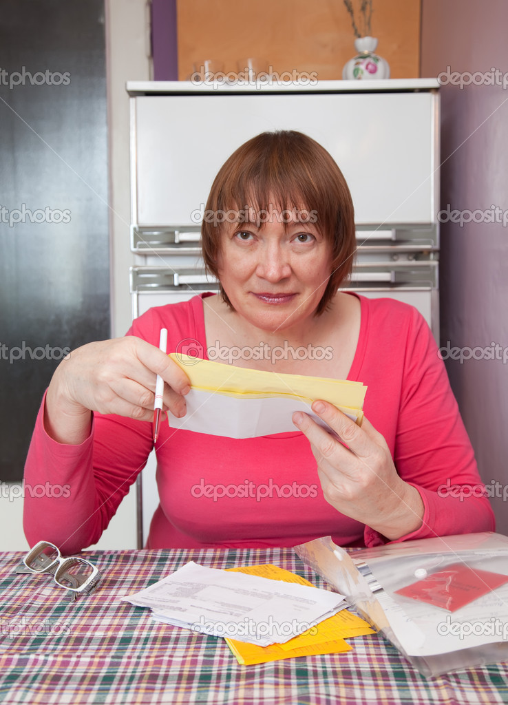 Sad mature woman with utility bills  at her home  Stock Photo #5434650