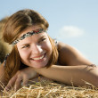 Stock Photo: Girl laying on hay bail