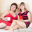 Royalty-Free Stock Photo: Women on sofa drinking tea