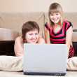 Royalty-Free Stock Photo: Happy girls using laptop in home