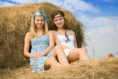 Farm girls on hay — Stock Photo