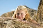 Girl on fresh hay — Stock Photo