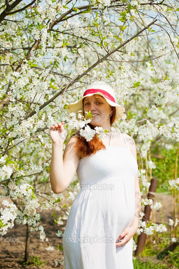 Portrait of 6 months pregnant woman in blossoming garden — Stock Photo #5713197