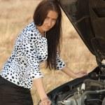 Woman looking under car hood — Stock Photo