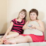 Women looking TV and drinking tea — Stock Photo #5722265