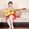 Woman with guitar in home — Stock Photo