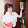 Woman selecting book in bookcase — Stock Photo #5722361