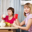 Women have tea in kitchen — Stock Photo