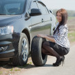 Woman during wheel changing — Stock Photo #5728582