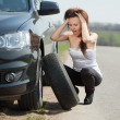 Woman during  wheel changing - Stock Photo