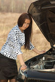 Woman looking under car hood — Foto Stock