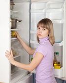 Woman taking apple from refrigerator — Stock Photo