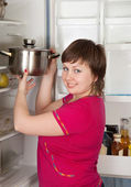 Woman putting pan into refrigerator — Stock Photo