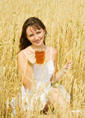 Girl with beer at cereals field — Stock Photo