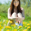 Happy girl sitting in meadow — Stock Photo #6037761