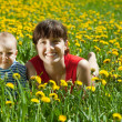 Mother with  baby in dandelion meadow — Stock Photo