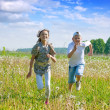 Teen friends running at meadow — Stock Photo