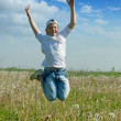 Happy teenager boy jumps at meadow — Stock Photo
