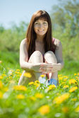 Happy girl sitting in meadow — Stock Photo
