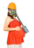 Woman in hardhat and gas-mask holding pregnant belly — Stock Photo