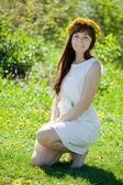 Smiling woman kneeling outdoor — Stock Photo