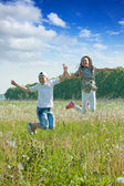 Boy and girl jumping at meadow — Stock Photo