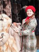 Girl chooses a fur coat — Stock Photo