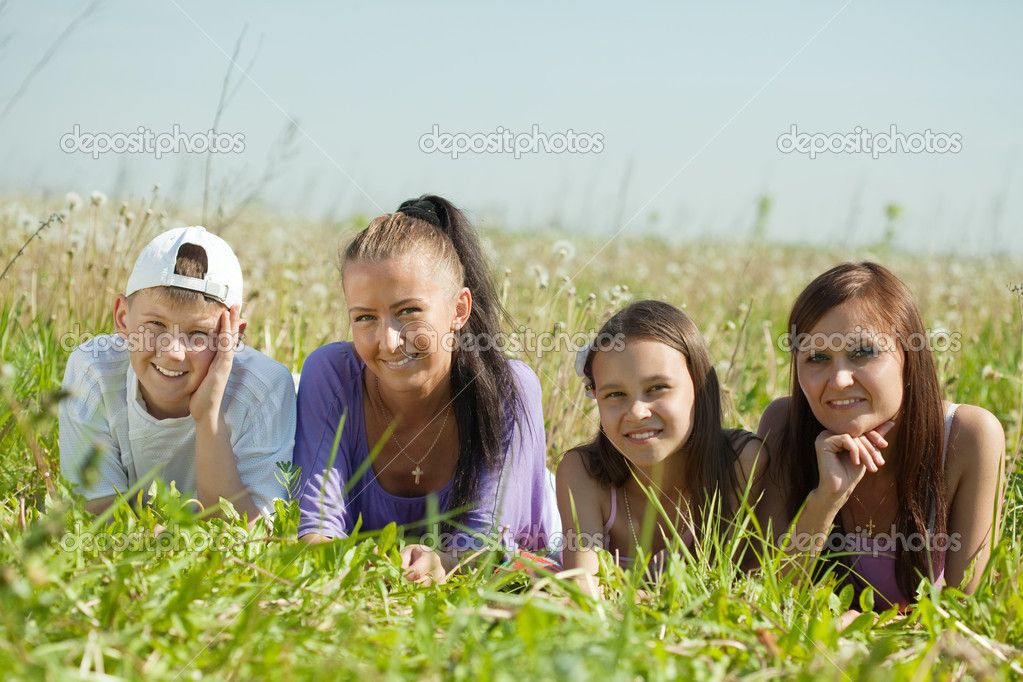 Two happy  women with teens laying in grass — Stock Photo #6037837