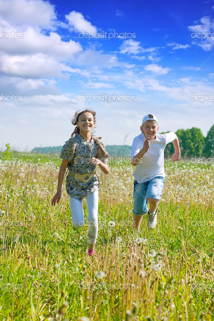 Teen friends running at meadow in summer  Stock Photo #6039326