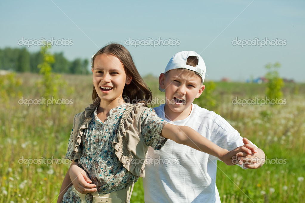Happy  teenager boy and girl together at meadow in summer — Stock Photo #6039440