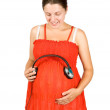 Foto Stock: Pregnant womwith headphones on tummy
