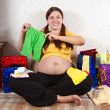 Pregnant woman with babies clothes — Stock Photo #6040449