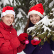 Women in Santa hats decorates fir-tree — Stock Photo