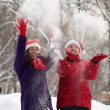Two women throw up snow — Stock Photo