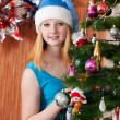Stock Photo: Girl in Santa hat near Christmas fir-tree