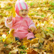 Baby with autumn leaves — Stok fotoğraf