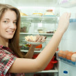 Girl putting snack into fridge — Stock Photo