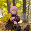 Girl with autumn leaves outdoors — Stock Photo