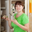 Woman putting with metal can near fridge - 图库照片