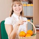 Businesswoman with basket of orange — Stock Photo #6042834
