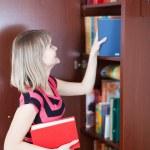 Girl selecting book in bookcase — Stock Photo #6043010