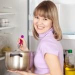 Woman eating from pan near fridge — Stock Photo #6043133
