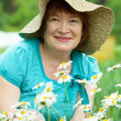 Happy mature woman in camomiles — Stock Photo #6044594