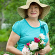 Happy mature woman with flowers — Stock Photo #6044644
